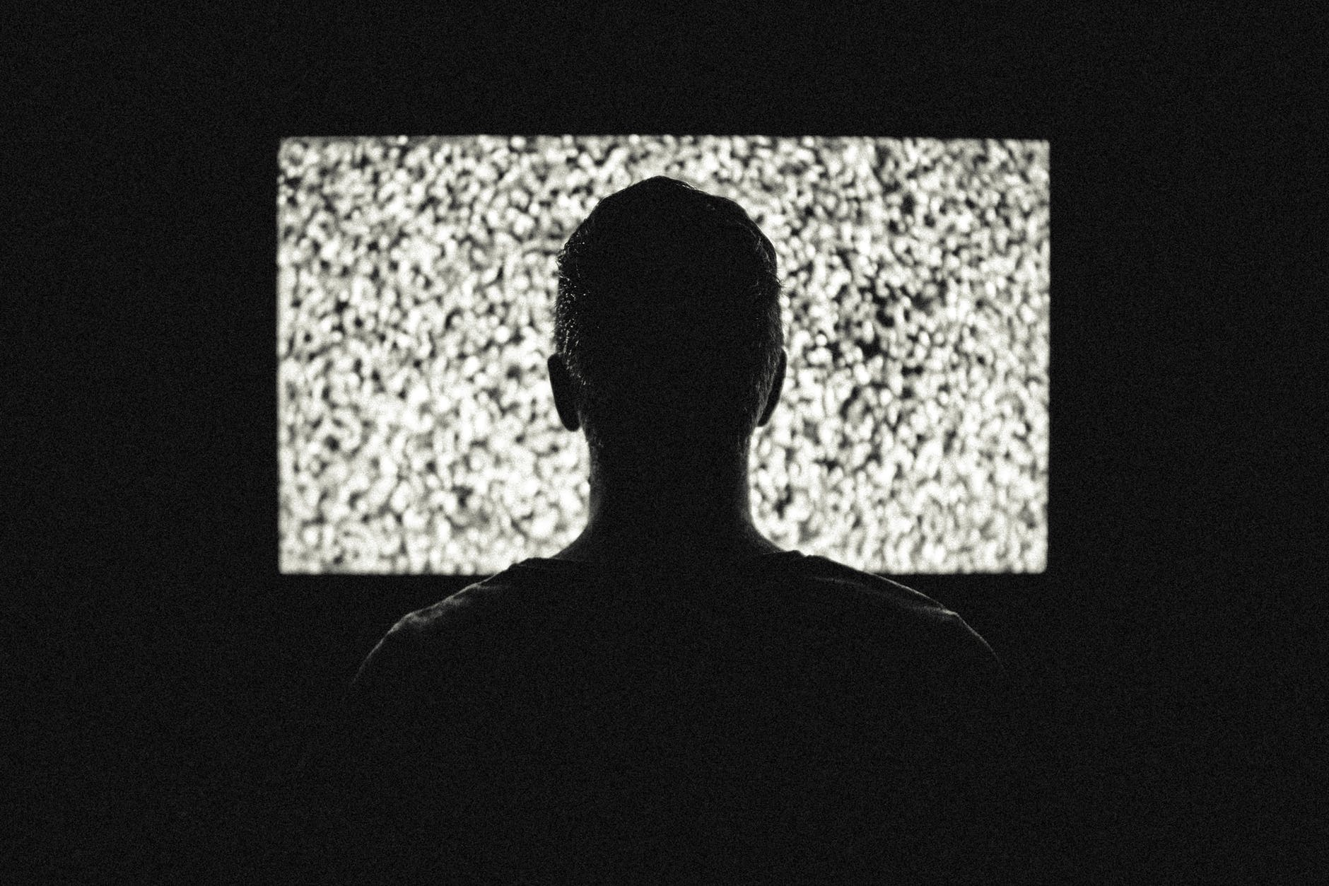 Man sitting in front of static on TV silhouette